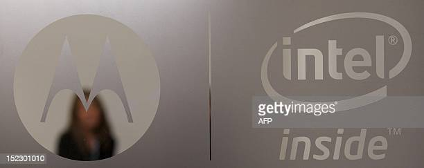 A woman is photographed through a door with Motorola and Intel branding logos during the press launch of the new Motorola RAZRi smartphone with an...