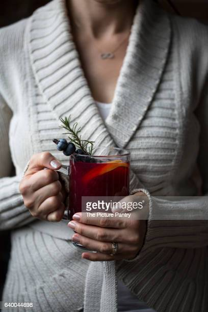 A woman is photographed with a glass of blueberry hot toddy in her hand