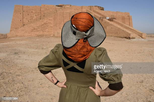 A woman is pictured on June 15 2020 in front of the Great Ziggurat temple a massive Sumerian stepped mudbrick construction dedicated to the moon god...