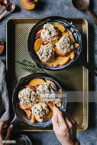 A woman is placing the last biscuit on top of peaches.