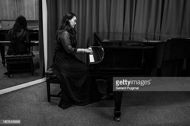 CONTENT] A woman is playing a piano in a small room She is wearing a black dress There is a mirror behind her reflecting her back