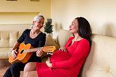 beautiful woman is enjoying playing acoustic