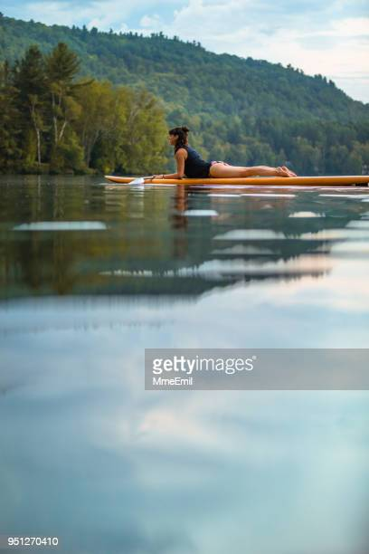 A woman is practicing SUP Stand-up Paddleboard Yoga on a lake. Cobra pose or Bhujangasana. Mauricie, Quebec, Canada