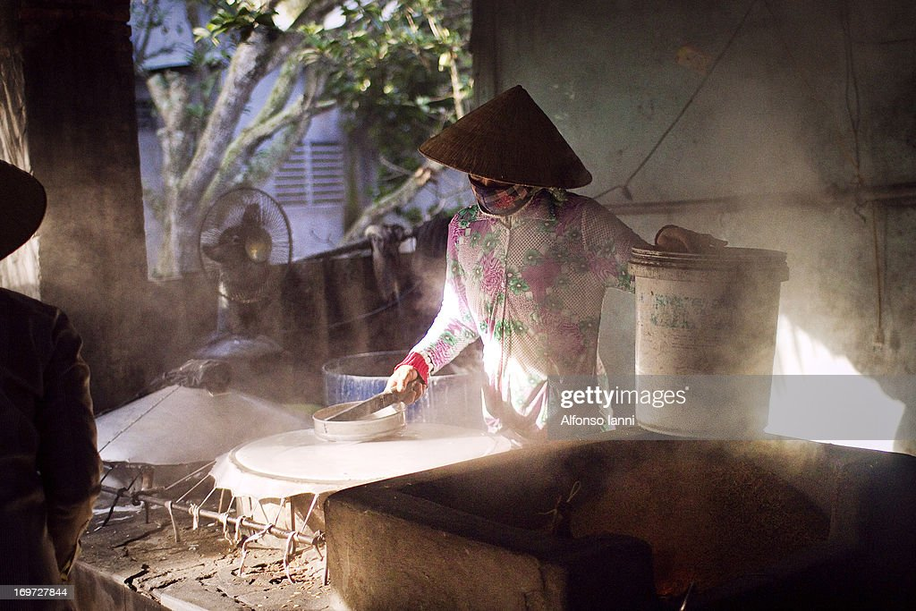 Woman is preparing Rice Noodles (making rice paper which will then be cut creating the noodles). In Vietnam(Mekong Delta).