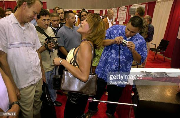 A woman is prodded from behind by the Orgasmo sex toy as men watch and take photographs at the fifth annual Erotica LA adult entertainment trade show...