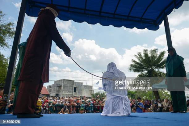 TOPSHOT A woman is publicly flogged in front of a mosque in the provincial capital Banda Aceh on April 20 2018 A group of amorous couples and...