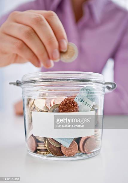 Woman is putting coin into savings box