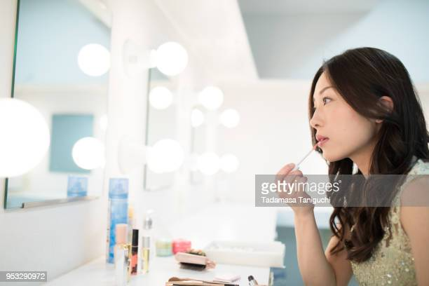 woman is putting on make up at backstage dressing room. - 舞台裏 ストックフォトと画像