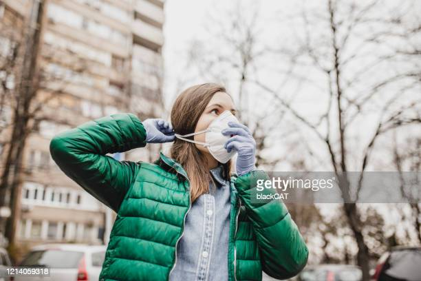 woman is putting protection mask from virus - cat face mask stock pictures, royalty-free photos & images