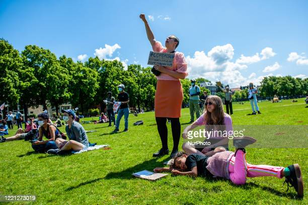 Woman is raising her hand during one of the speeches gaven, during the Refugee Lives Matter demonstration in Amsterdam, Netherlands on June 20th,...