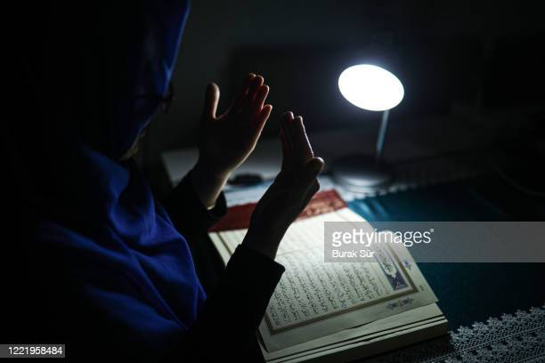woman is reading quran in ramadan. she prays with her hands open and be thankful - pakistan stock pictures, royalty-free photos & images