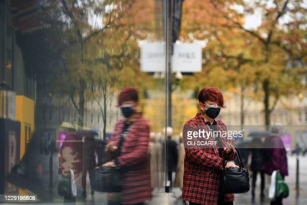 Woman is reflected in a window as she leaves a shop in central Sheffield, south Yorkshire on October 21 prior to further lockdown measures as the...