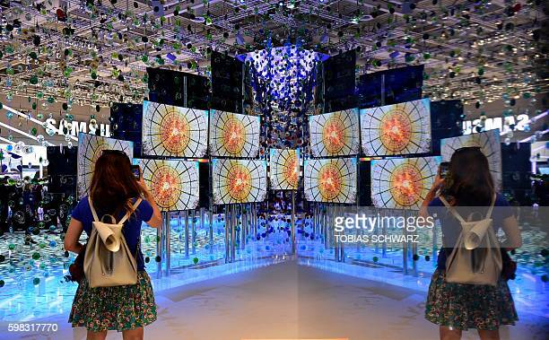 A woman is reflected in front of a screen installation at the booth of Samsung at the IFA electronics trade fair in Berlin on September 1 2016 The...