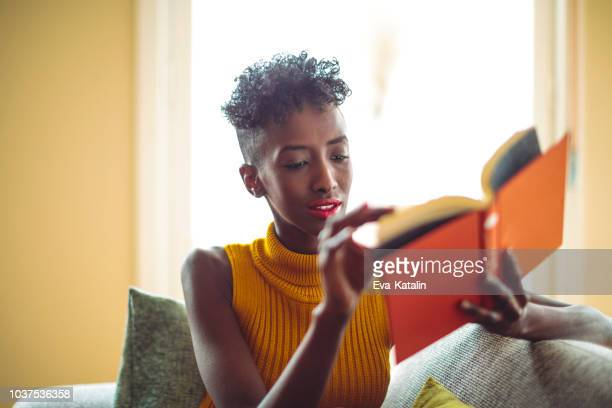 woman is relaxing and reading a book - literature stock pictures, royalty-free photos & images