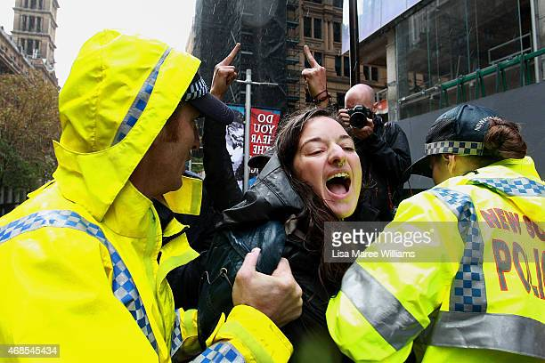 A woman is removed by police from the Martin Place stage after storming the area to speak out against 'Reclaim Australia' protesters on April 4 2015...