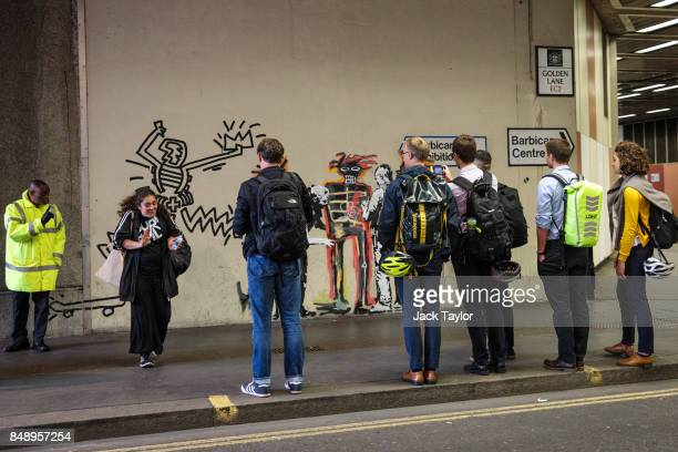 A woman is reprimanded by a security guard for touching a new work by street artist Banksy on a wall by the Barbican Centre as members of the public...
