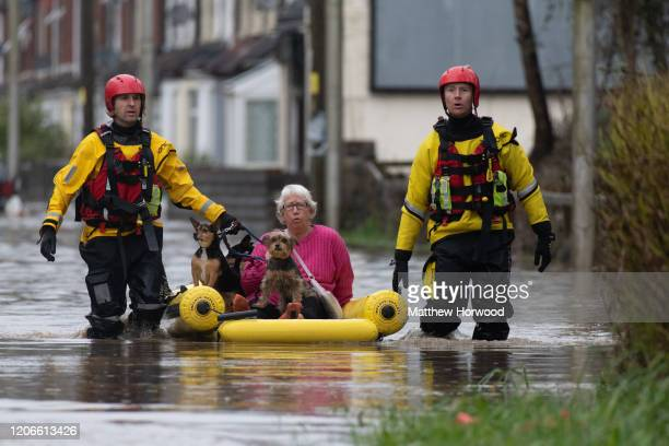 A woman is rescued from a property on Oxford Street on February 16 2020 in Nantgarw Wales The Met Office have issued a red weather warning for rain...