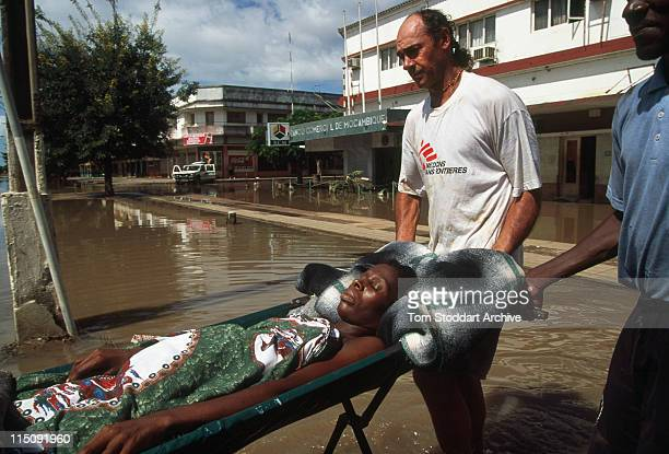 A woman is rescued from a roof top and is carried by Medicins Sans Frontieres workers through filthy flood water in Chokwe after rains engulfed...