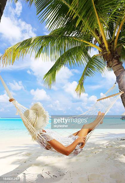Woman is resting in hammock near the sea.