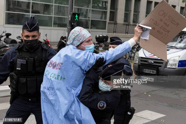 """Woman is restrained by police as operating room nurses protest the """"contempt"""" shown to them in a overhaul of France's healthcare system, the """"Ségur..."""