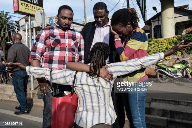 TOPSHOT A woman is reunited with her family after her evacuation from DusitD2 compound in Nairobi after a blast followed by a gun battle rocked the...