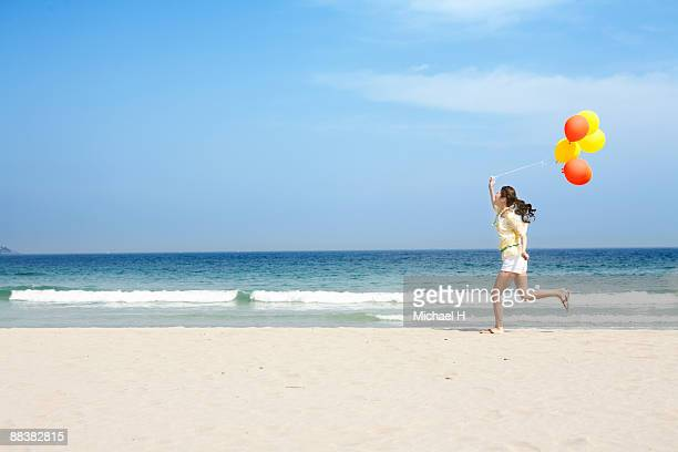 A woman is running on the beach with the balloon.