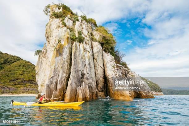 A woman is sea kayaking the coastline of Abel Tasman National Park