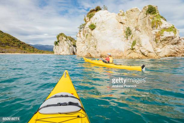 A woman is sea kayaking the coastline of Abel Tasman National Park