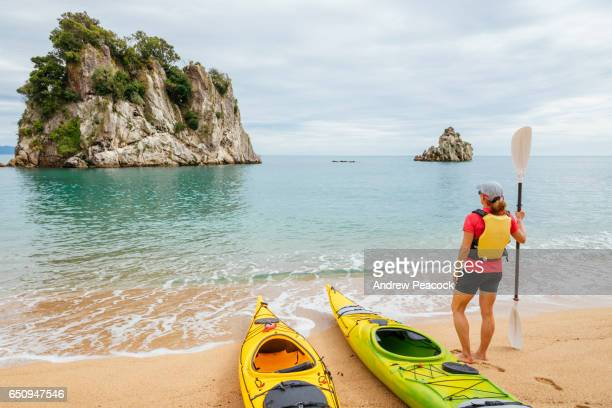 a woman is sea kayaking the coastline of abel tasman national park - nelson city new zealand stock pictures, royalty-free photos & images