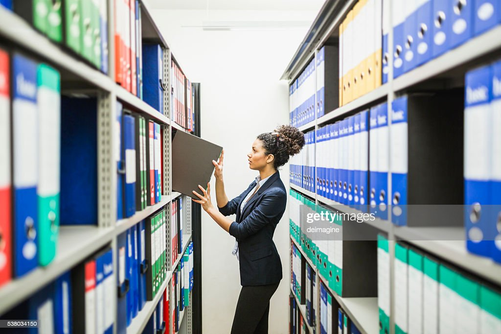 Woman is searching for files in paper archive : Stock Photo