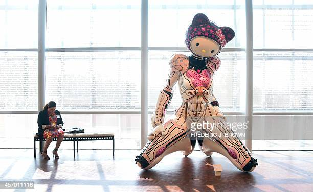 A woman is seated beside a display of 'Super Space Titan Kitty' a 2014 fiberglass sculpture by Colin Christian displayed at a press event ahead of...