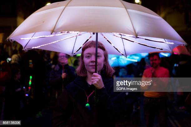 A woman is seen are she's holding an lighting umbrella during the Leeds festival Light Night Leeds is an annual free multiarts and light festival...