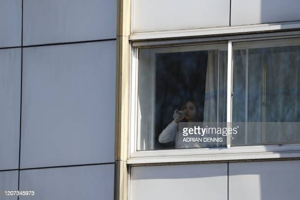 A woman is seen at the window of a boardedoff Holiday Inn hotel close to Heathrow Airport west of London on March 16 2020 which was blockbooked by...