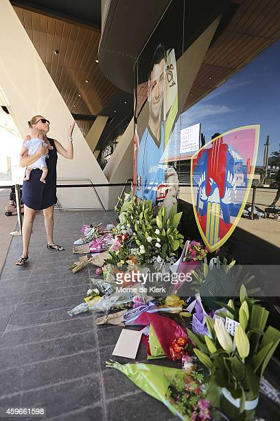 A woman is seen blowing a kiss after lying flowers amongst other tributes next to a photograph of Phil Hughes outside the Adelaide Oval on November...
