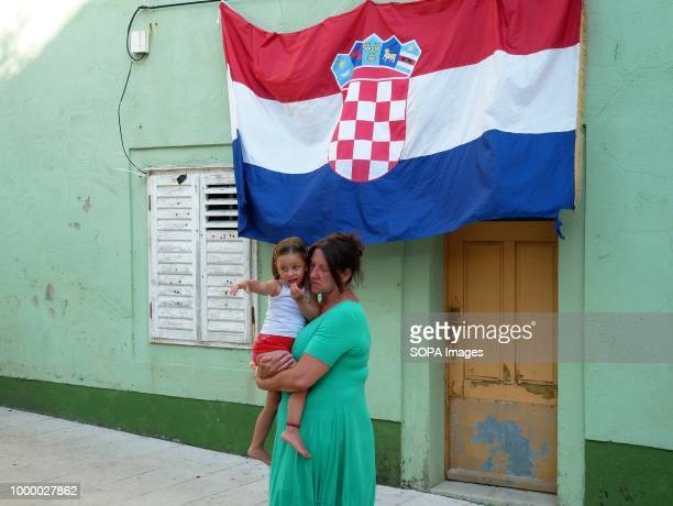 A woman is seen carrying a kid next to a Croatian flag Croatians in the Island of Pag watched the world cup football final match Croatia vs France...