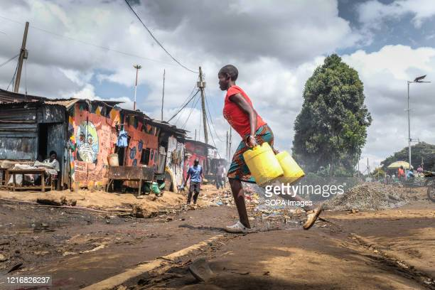 A woman is seen carrying her water jerrycans along the Street during the Madaraka day Celebration Just like many other Holidays have always been...