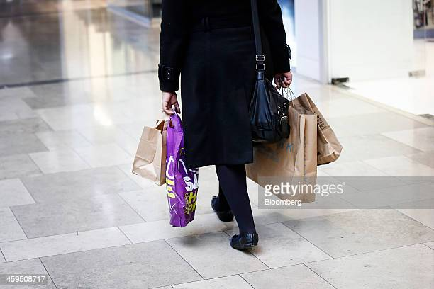 A woman is seen carrying shopping bags after purchasing goods in the Christmas sales at the Westfield Stratford City mall in London UK on Friday Dec...
