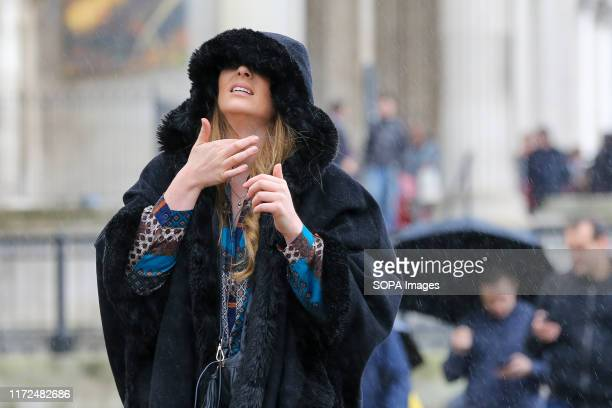 A woman is seen covering her head with a winter jacket as it starts raining in Trafalgar Square
