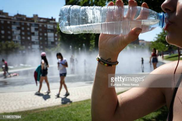 A woman is seen drinking water as people are refreshing themselves in the water streams of Madrid Rio a day before it's expected that a heatwave that...