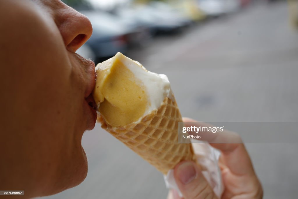 A woman is seen eating mango flavoured ice cream in a gluten free cone on 19 August, 2017.