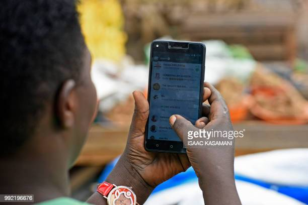 A woman is seen going through her WhatsApp account on her phone in Kampala on July 5 2018 Politicians clerics feminists and others have formed a...