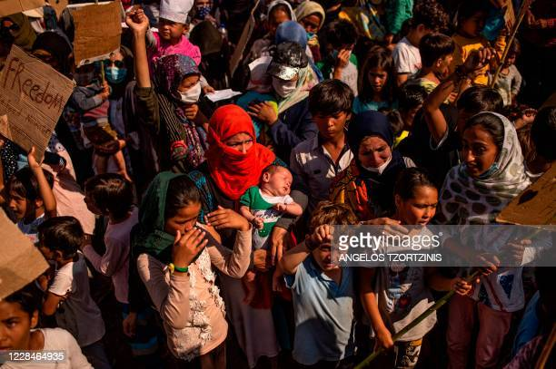 Woman is seen holding a baby as refugees and migrants from the Moria camp protest near Mytilene on the Greek island of Lesbos, on September 12 a few...