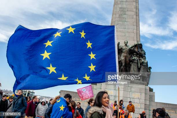 A woman is seen holding a flag of the EU in front of the monument at the Poulaert square during the protest A day before the anniversary of the...