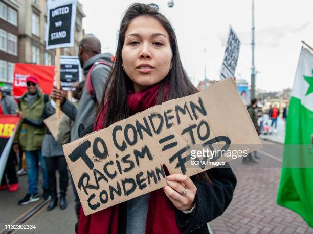 A woman is seen holding a placard against the far right political party FvD during the demonstration Thousands of people gathered at the Dam square...