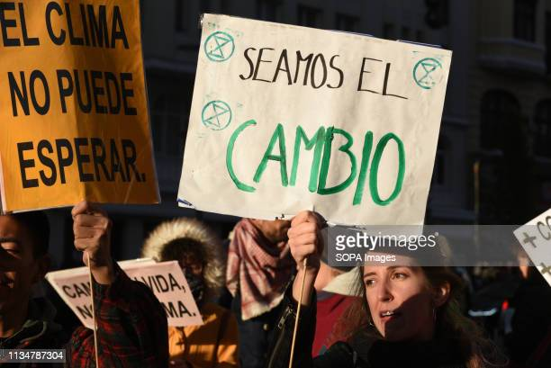 A woman is seen holding a placard reading 'Somos el Cambio' during the protest Activists from group Extinction Rebellion gathered at Callao square in...