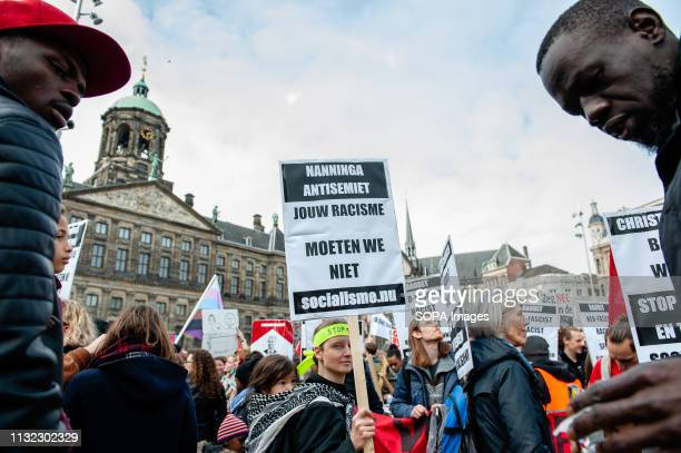 A woman is seen holding a placard while holding a baby on her back during the demonstration Thousands of people gathered at the Dam square in the...