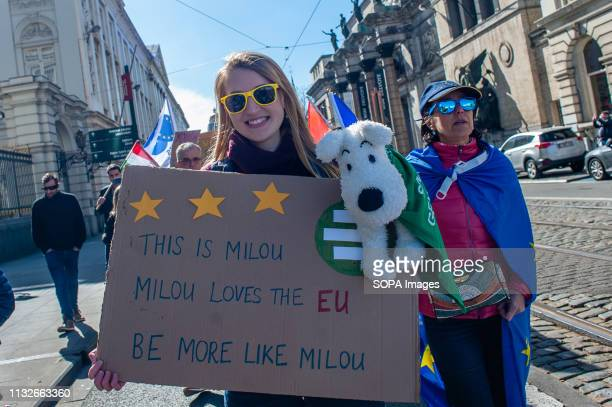 A woman is seen holding a placard with a Milou stuffed dog during the protest A day before the anniversary of the founding Treaty of the European...