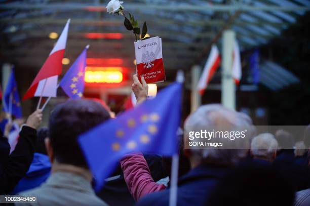 A woman is seen holding a polish constitution during the protest People demonstrate against reforms of the Supreme Court and demand for free courts...