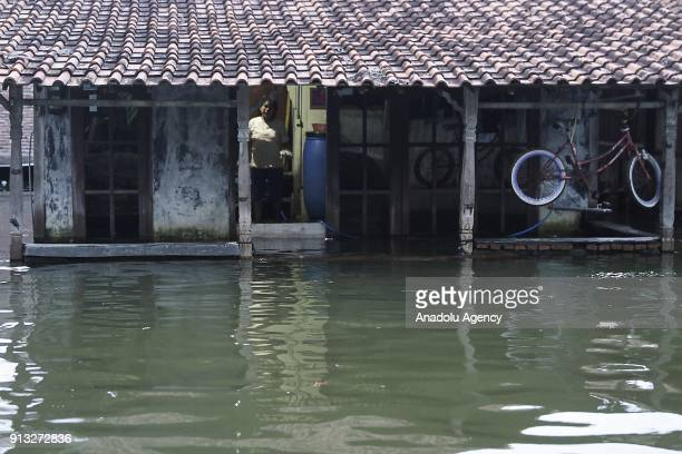 A woman is seen inside her waterlogged house in Sriwulan village Sayung subdistrict of Demak regency Central Java Indonesia on February 2 2018 Local...