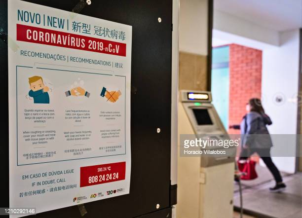 A woman is seen leaving the premises near a trilingual poster in Portuguese English and Chinese with instructions on Coronavirus prevention hanging...